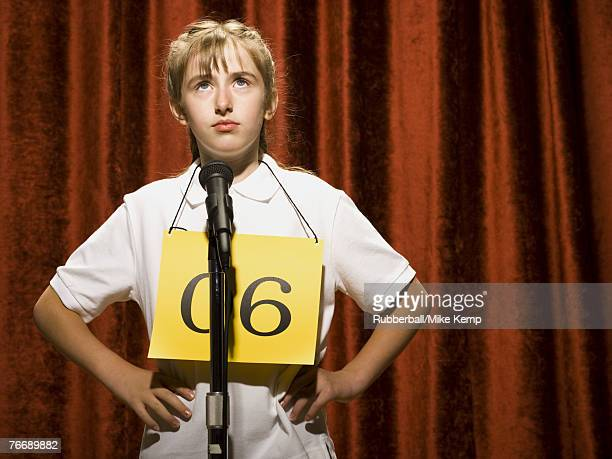 Girl contestant standing at microphone thinking