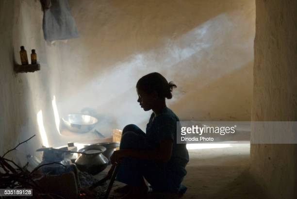 Girl cooking food inside a kitchen in Uttar Pradesh, India.