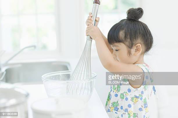 Girl cooking with eggbeater, side view