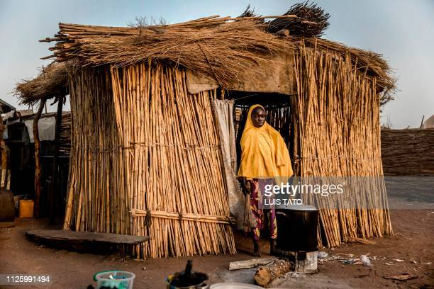 TOPSHOT A girl cooks in front of her house at Malkohi refugee camp in Jimeta Adamawa State Nigeria on February 19 four days ahead of the country's...