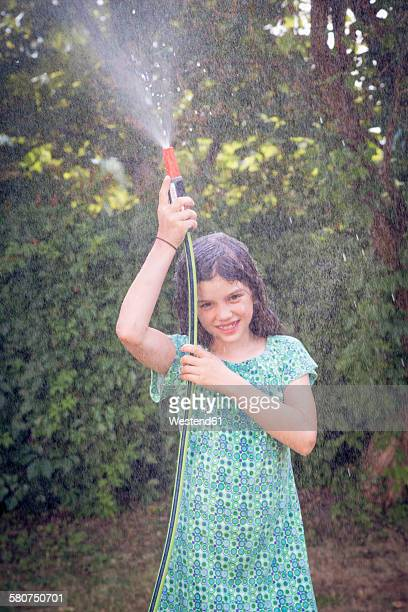 Girl cooling herself with garden hose