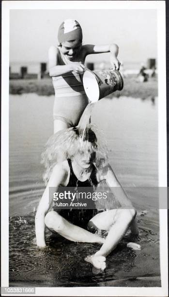 Girl cools another girl down by pouring a bucket of water over her head during a holiday on the beach at Bridlington.