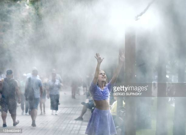 Girl cools down herself at a water sprinkler in the center of Ukrainian capital of Kiev during hot summer day on August 10, 2021.
