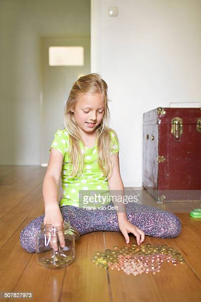 Girl counting coins from savings jar