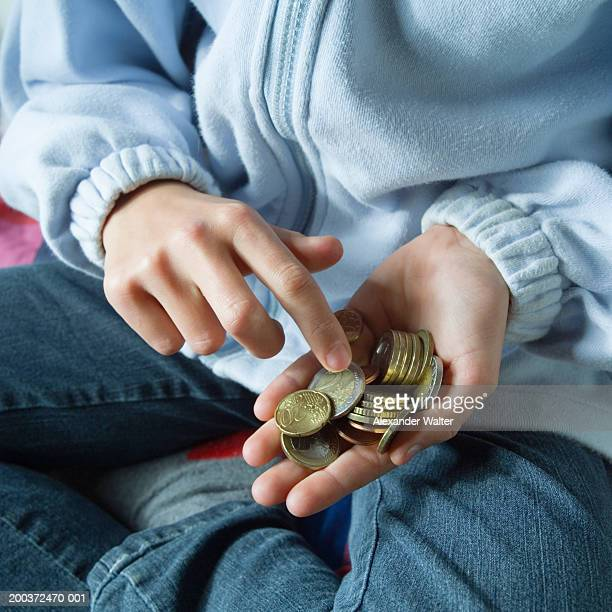 Girl (8-10) counting coins in hand, close-up