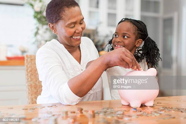 Girl (6-7) counting coins with grandmother, Cape Town, South Africa