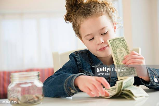 Girl (10-11) counting her savings
