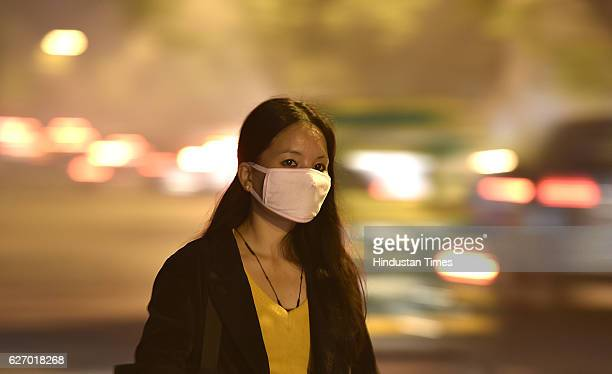 A girl cover her face with Mask during the Heavy fog or Smog at Janpath Sector10 on December 1 2016 in New Delhi India Traffic was moving slowly...