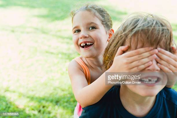 Girl covering boy's eyes