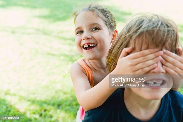 girl covering boy's eyes - augen zuhalten stock-fotos und bilder