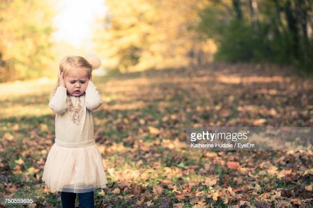 Girl Covering Ears With Hands While Standing On Field During Autumn