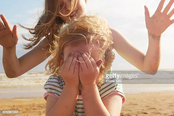 Girl covering eyes in front of sister on beach, Camber Sands, Kent, UK
