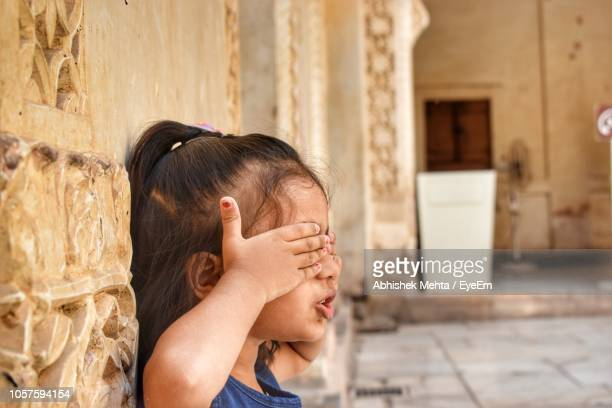 Girl Covering Eyes With Hands In Corridor