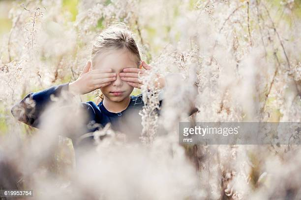 Girl covering eyes with hands