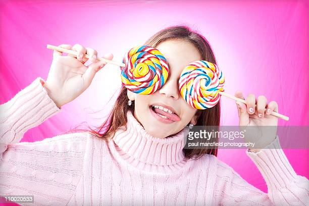 Girl covering eyes with lollies