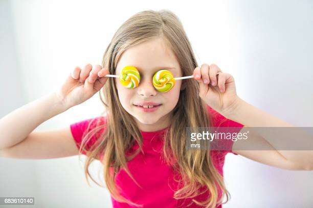 Girl covering eyes with lollypops
