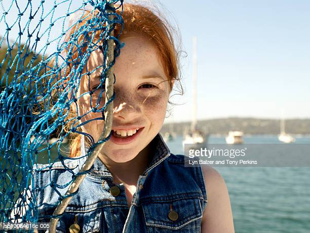 Girl (10-11) covering face with fishing net, portrait