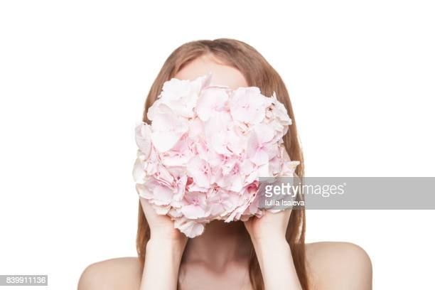 Girl covering face with flowers