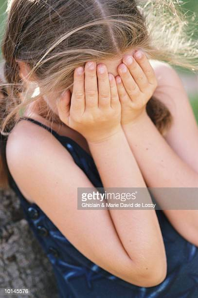 Girl (8-10) covering face with hands, elevated view