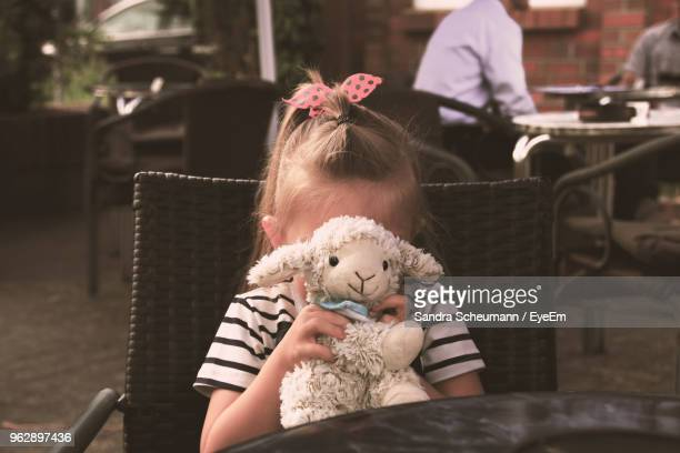 girl covering face with toy while sitting at cafe - soft toy stock pictures, royalty-free photos & images