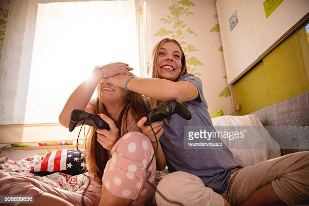 Girl covering friend's eyes in the middle of computer game