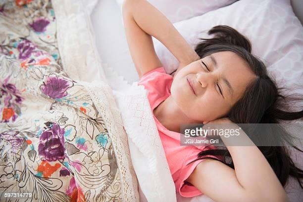 Girl covering her ears in bed