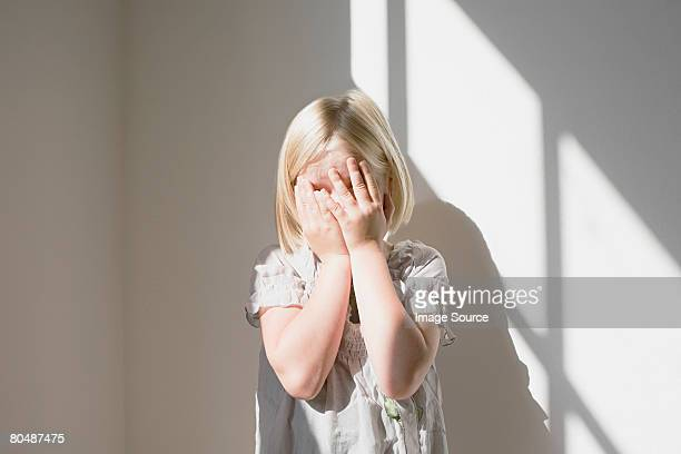 Girl covering her face her hands