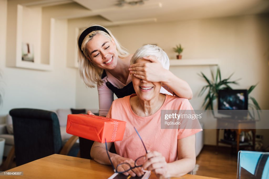 Girl covering mother's eyes and giving her present : Stock Photo