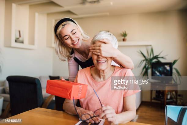 girl covering mother's eyes and giving her present - mother's day stock pictures, royalty-free photos & images