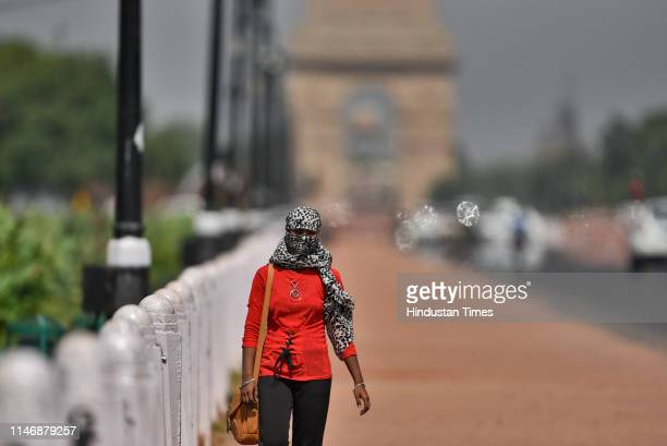 A girl covers her head with a scarf to protect herself from the scorching heat wave as mercury touched 44 degree celsius at Rajpath on May 29 2019 in...