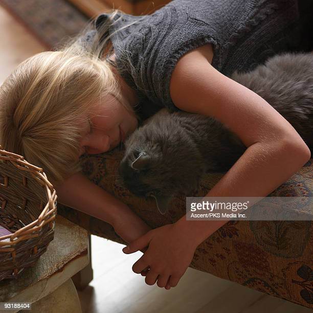 Girl cradles cat while sleeping on ottoman