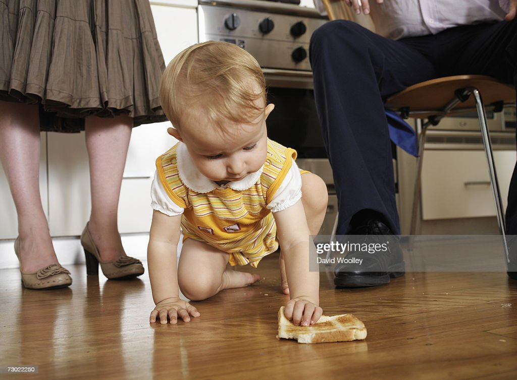 Girl (9-12 months) crawling on floor in kitchen with parents, low section : Stock Photo