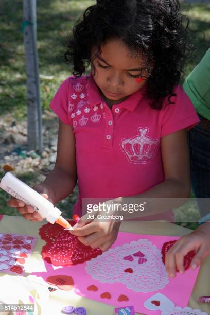 A girl creating a picture at the arts and craft booth at the United Hearts Family Festival