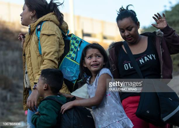 TOPSHOT A girl cries as a group of Central American migrants surrender to US Border Patrol agents after jumping over the metal barrier separating...