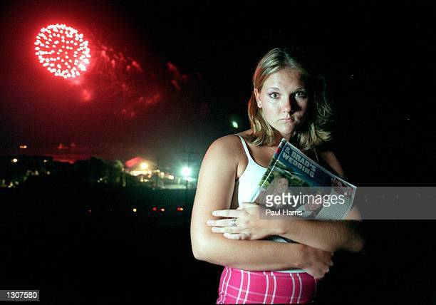 A girl cries July 29 2000 while holding a press clipping of Bradd Pitts and Jennifer Aniston''s wedding in Malibu CA Behind her is a firework display...