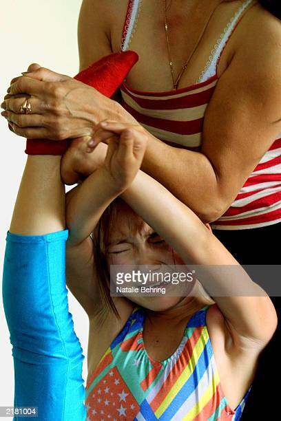 A girl cries out as her instructor Otgoo stretches her leg during a contortion class at the Mongolian State Circus July 18 2003 in Ulan Bator...