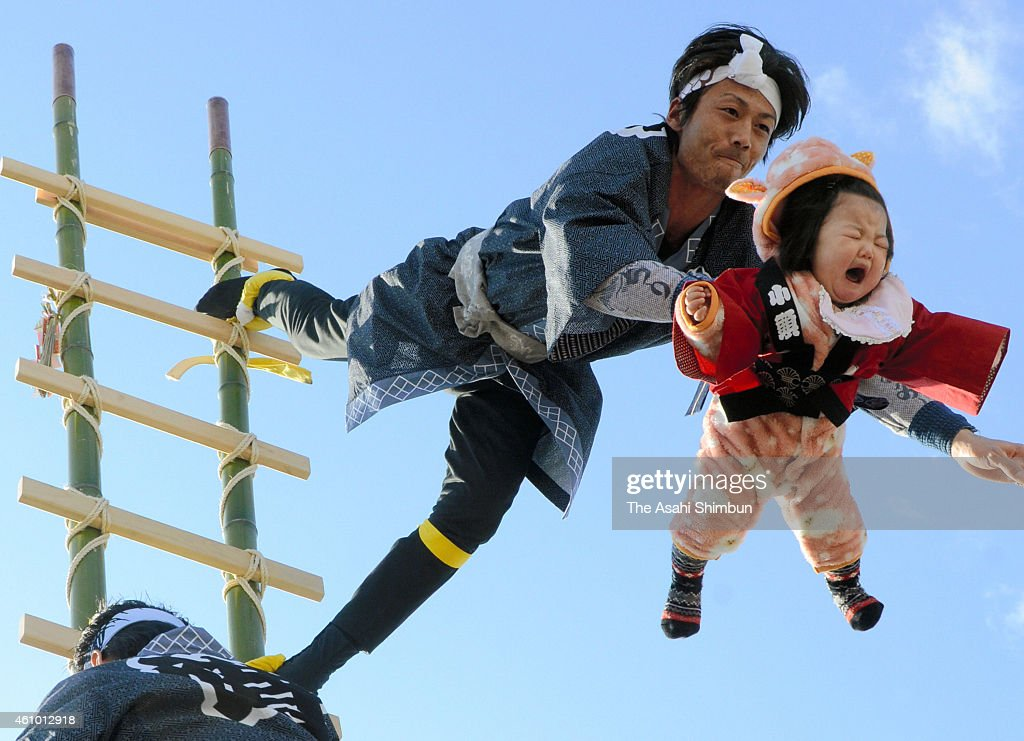 A girl cries with fear as a member of fire companies performs the stunt called 'Tsuru-kame', which a man holds a kids on the ladder, during the New Year fire review at Otsu Park on January 4, 2015 in Kofu, Yamanashi, Japan.