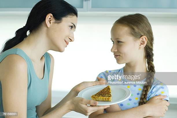 'Girl crossing arms, looking at woman holding piece of quiche'