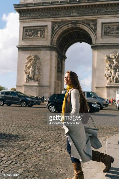 Girl crossing busy street in front of the Arc de Triomphe
