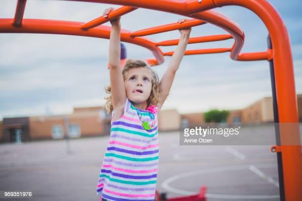 Girl crossing monkey bars