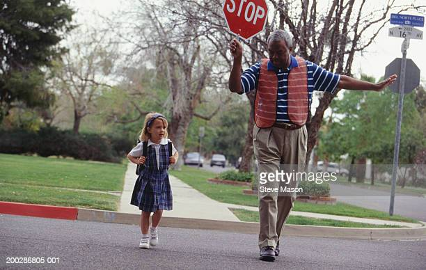 Girl (4-5) crossing street with crossing guard