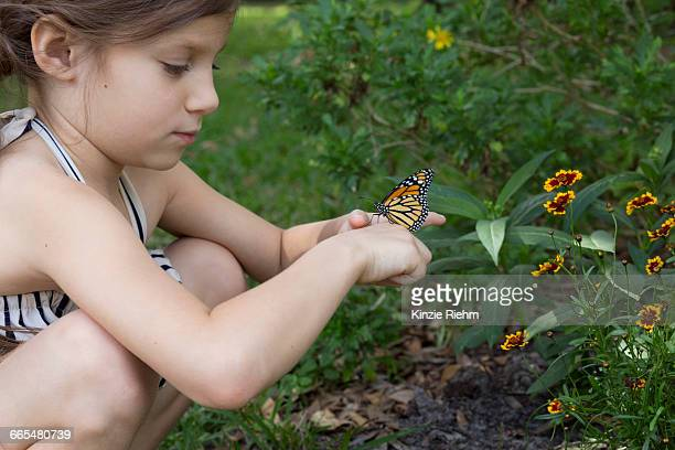 Girl crouching holding monarch butterfly
