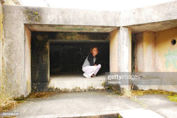 Girl crouching in concrete cubby