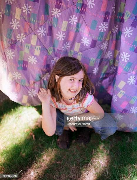 Girl crouching in front of hanging blanket