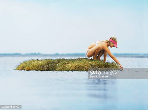 Girl (9-11) crouching on grass island dipping finger into sea