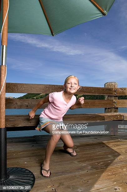 girl (10-11 years) crouching on wooden deck, portrait - 10 11 years stock pictures, royalty-free photos & images