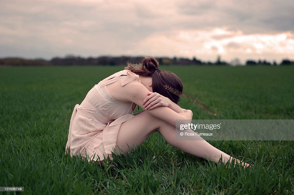 Girl crying in field at sunset with pink sky : Stock Photo