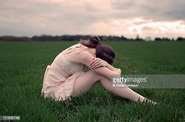 Girl crying in field at sunset with pink sky