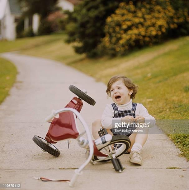 Mädchen weint, neben dem Dreirad