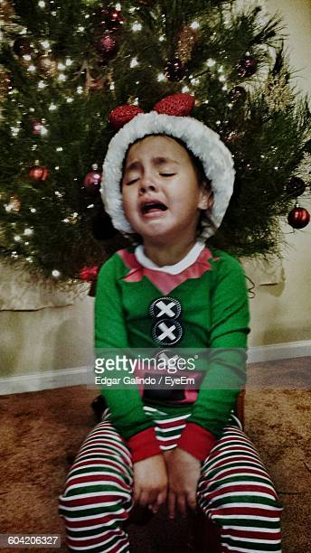 girl crying while sitting against christmas tree at home - sadgirl stock pictures, royalty-free photos & images